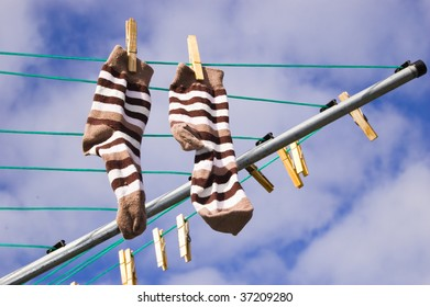A pair of freshly washed socks hang out to dry on a sunny day