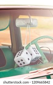 Pair of Fuzzy Dice Hanging from the Rearview Mirror of an Antique Car
