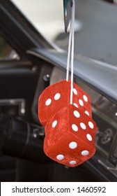 Pair of Fuzzy Red and White Dice hanging from the mirror of a vintage car.