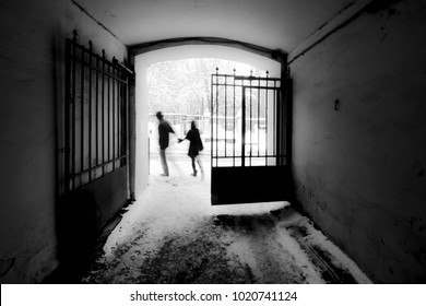 A pair of ghostly silhouettes comes out from the arch onto the snow-covered street. Black and white photography.
