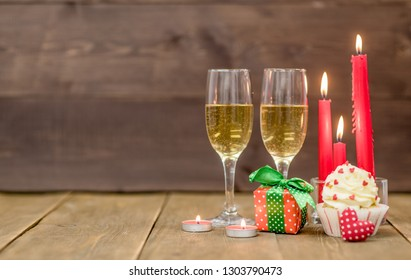 Pair Glass Of Champagne With Cupcakes Gift Box And Candles Wooden Background Empty