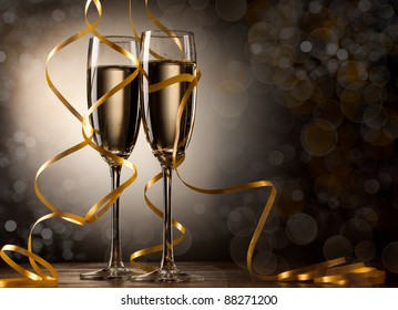 Pair glass of champagne. New year celebration or wedding concept theme. Paper streamer with defocused lens blur over background. Celebration concept.