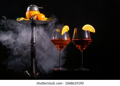 Pair of glasses with alcoholic drink beverage wine cocktail and hookah with fruits black background isolated