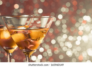 a pair of glasses of fresh cocktail with ice on  light bokeh background with space for text
