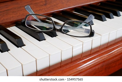 A pair of glasses on a piano