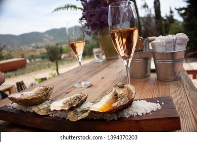 Pair of glasses one with sparkling pink wine  placed on wooden table for pairing with oysters cooked in gourmet style