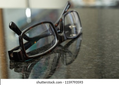A pair of glasses reflected on a marble desk