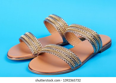 Pair of gold color woman sandals isolated ob blue background