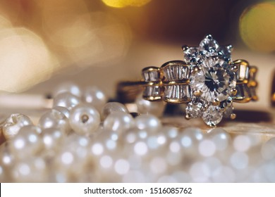 Pair of gold wedding rings with diamonds on pearl background with bokeh,Vintage picture style