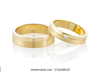Pair of gold wedding rings isolated on white background. Yellow gold ring bands with combined glossy and textured surface