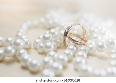 A pair of gold wedding rings on pearls