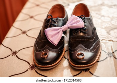 Pair of gold wedding rings and pink bowtie on the black shoes