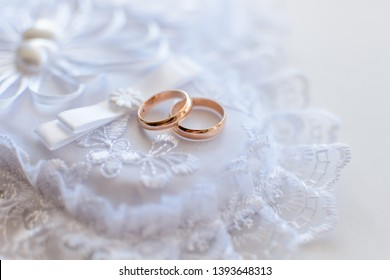 pair of gold wedding traditional rings on a white lace cushion on marriage registration