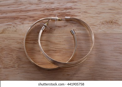 a pair of golden Ear Ring on Wood Background