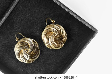Pair of golden earrings in black jewel box closeup