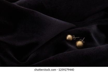 Pair of golden round earrings on velvet dark fabric