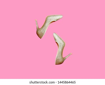 Pair of golden sparkling shoes on bright pink background. Fashion female footwear for party