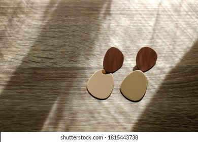 Pair of golden statement earrings, illuminated by sunlight. Selective focus.