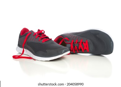 A pair of gray running shoes with red shoelaces on a white background