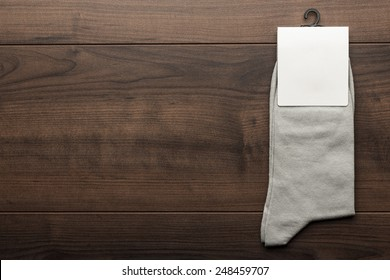 pair of gray socks with blank packing on the wooden table