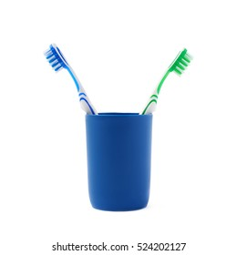 Pair of green and blue toothbrushes in blue plastic cup isolated over white background, quarrel conflict problem
