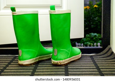 Pair of green child rubber boots standing indoors near open door.