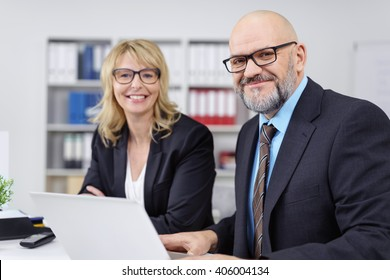 Pair of grinning mature male and female professionals dressed formally in suit jackets discussing something at desk or table