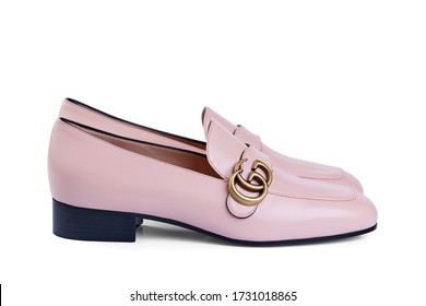 Pair of Gucci women's shoes made of thin soft pink leather with a low heel, isolated on a white background with a light shadow. Side view. Belarus, Minsk, 22.04.2020.