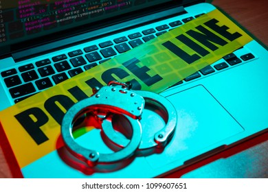 A pair of handcuffs and police line tape sit atop a laptop keyboard. Technology/cyber crime concept.