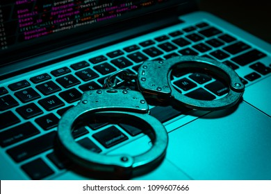 A pair of handcuffs sit atop a laptop keyboard. Technology/cyber crime concept.