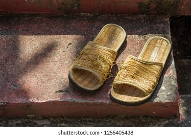 Pair of handmade woven flipflop on the floor is torn and partly damage