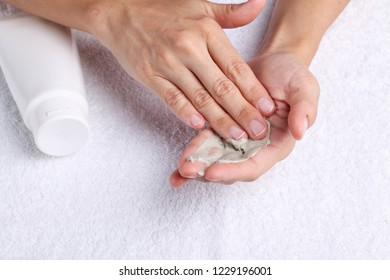 A pair of hands applying hand cream