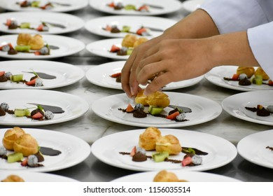 A pair of hands decorating desert plates of profiteroles and fruit garnishes.