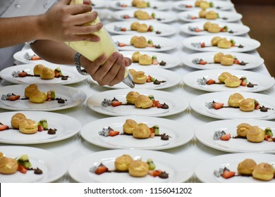 A pair of hands garnishes a plate of choux pastry with vanilla cream
