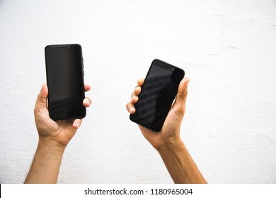 Pair of hands holding and showing mobile phones and rising them up against white wall
