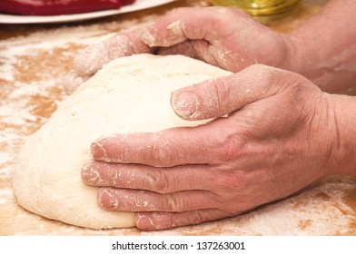 Pair of hands kneading dough