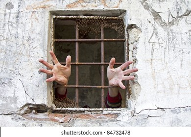 A pair of hands pleading for help at the prison window