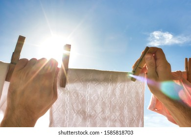A pair of hands reaching up to hang a white shirt on a washing line