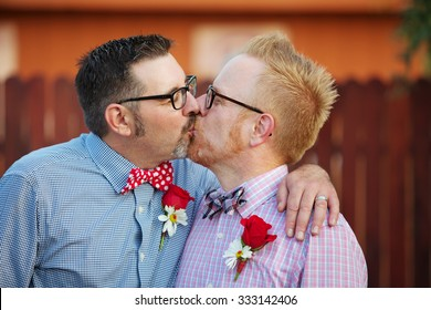 Pair of happily married gay men kissing outdoors