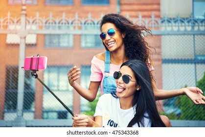 Pair of happy friends making funny faces while taking a self portrait outside with pink cell phone attached to selfie stick pole