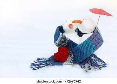 pair of happy snowmen walking together wrapped in scarf under an umbrella in winter sunny / day of all lovers