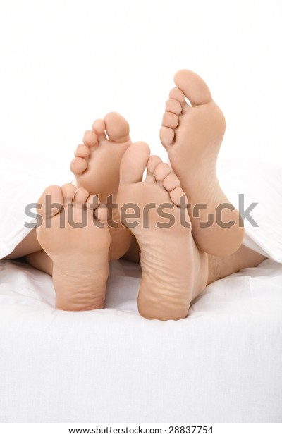 Pair heels are visible under a white bed-sheet, isolated