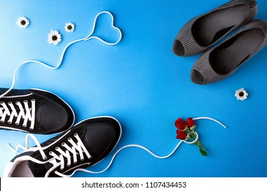 A pair of women's high heel shoes and a pair of men's sneakers with a heart shape from laces and a bouquet of roses on blue background. Message of love confession, Valentine's day concept. Copy space