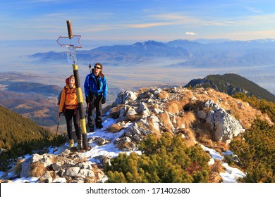 Pair of hikers on rocky mountain summit