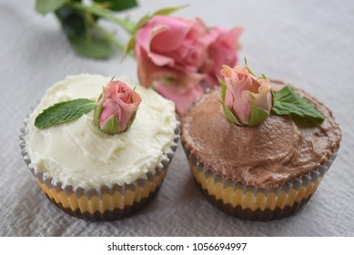 A pair of homemade cupcakes in contrasting frosting colors white and brown decorated with fresh pink roses that creates a soft romantic feeling.