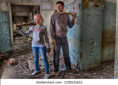 A pair of hooligans: beautiful girl in bright makeup (red lipstick and dark eye shadows) with a bat and a guy with a sledgehammer, standing in the middle of the ruins of an  building. Band fighters