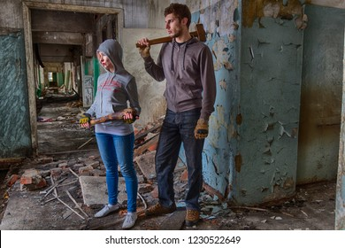 A pair of hooligans: a girl in hood with a bat and a guy with a sledgehammer, standing in the middle of the ruins of an old building. Maybe street band or fighters