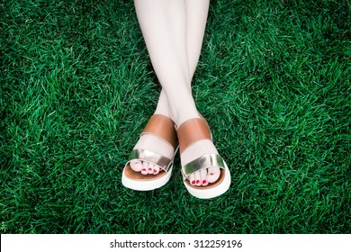 A pair of human legs (female) with shoes lying crosswise in a soft, deep green grass.