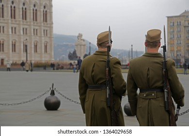 Pair of Hungarian military soldiers are patrolling and scanning the Kossuth Lajos square in Budapest,for threats and to intimidate possible criminals.Their khaki uniform and bayonet rifle are visible.