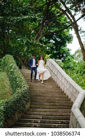 A pair of interracial lovers run down stone steps in the park during the day. An Indian man is marrying a Chinese woman and they are running down the stairs in delight and joy.